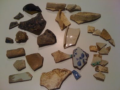 Pieces of ceramics, porcelain, china, salt glaze ceramic, and green bottle glass found on the surface